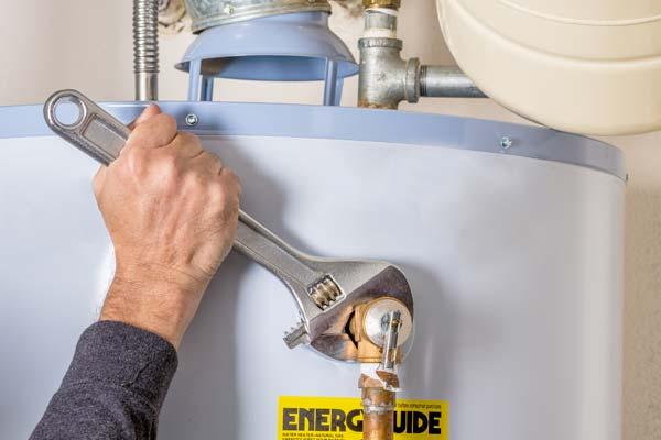 man-fixing-hot-water-tank